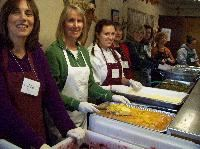 Volunteers serving food at Loaves & Fishes Tuesday